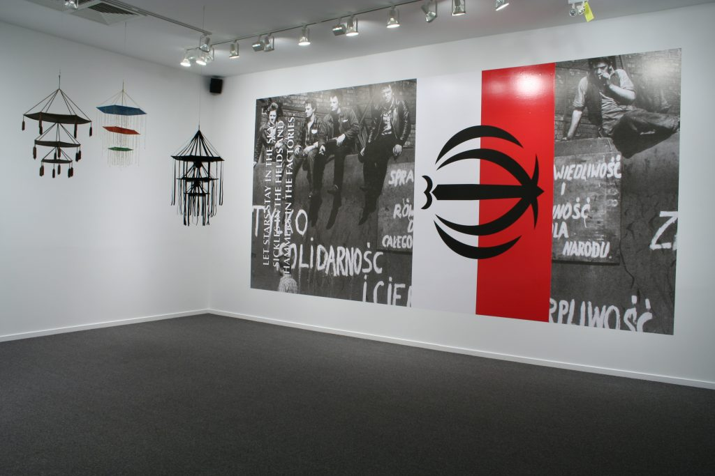 (L to R) Pajaki, 2011, variable materials, dimensions and Only Solidarity and Patience Will Secure Our Victory, 2010, print on vinyl, 3 x 6 m