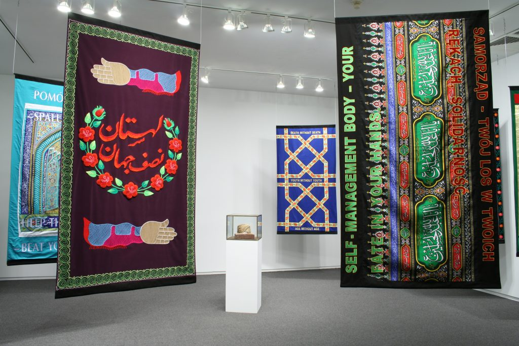 Wheat Molla, 2011, wheat, cotton, glue, brick, 45 x 35 x 25 cm, Friendship of Nations, 2011, banners, embroidered fabric, silkscreen, 200 x 120 cm, courtesy the Third Line Gallery, Dubai and Kraupa-Tuskany Zeidler Galerie, Berlin