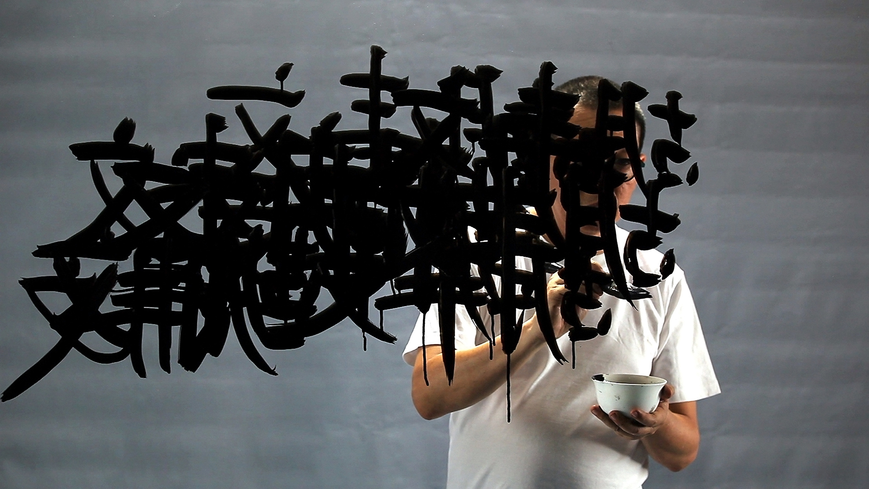 FX Harsono, 𝘞𝘳𝘪𝘵𝘪𝘯𝘨 𝘪𝘯 𝘵𝘩𝘦 𝘙𝘢𝘪𝘯, video still, 2011, courtesy the artist and Museum of Contemporary Photography