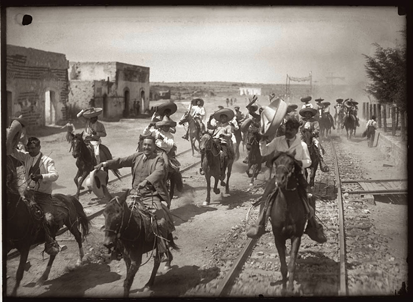 Francisco Madero's troops storming into a town on horseback,Mexico, ca.1911
